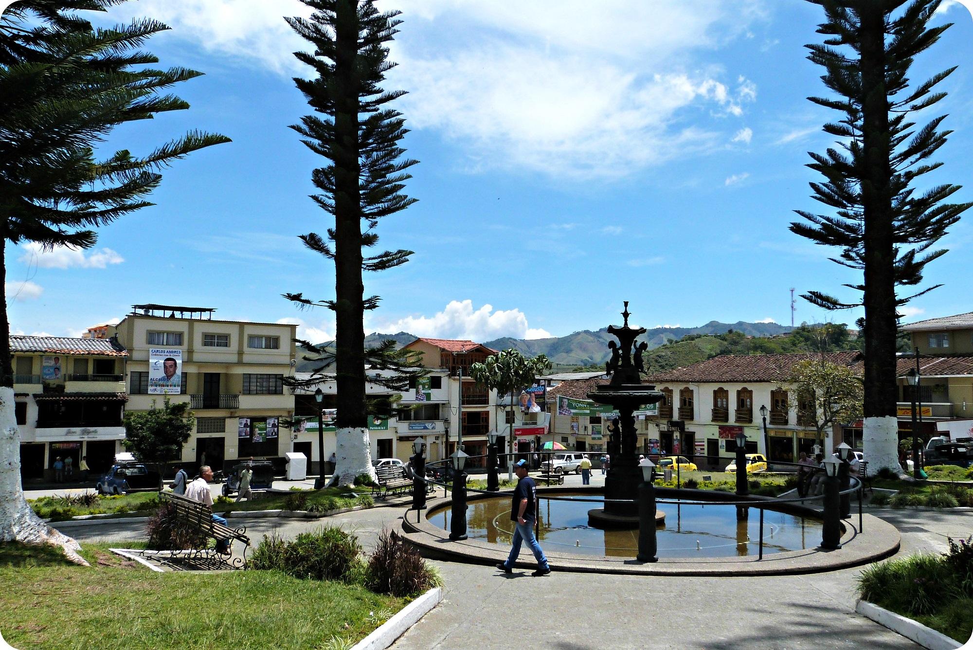 Place principale d'Aguadas avec une fontaine et de grands arbres
