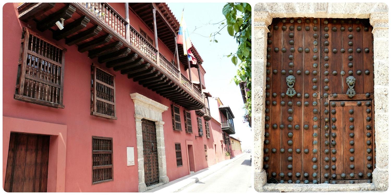 casa roja con una puerta de madera muy imponente llena de enormes clavos y de dos aldabas para tocar en una calle de Cartagena